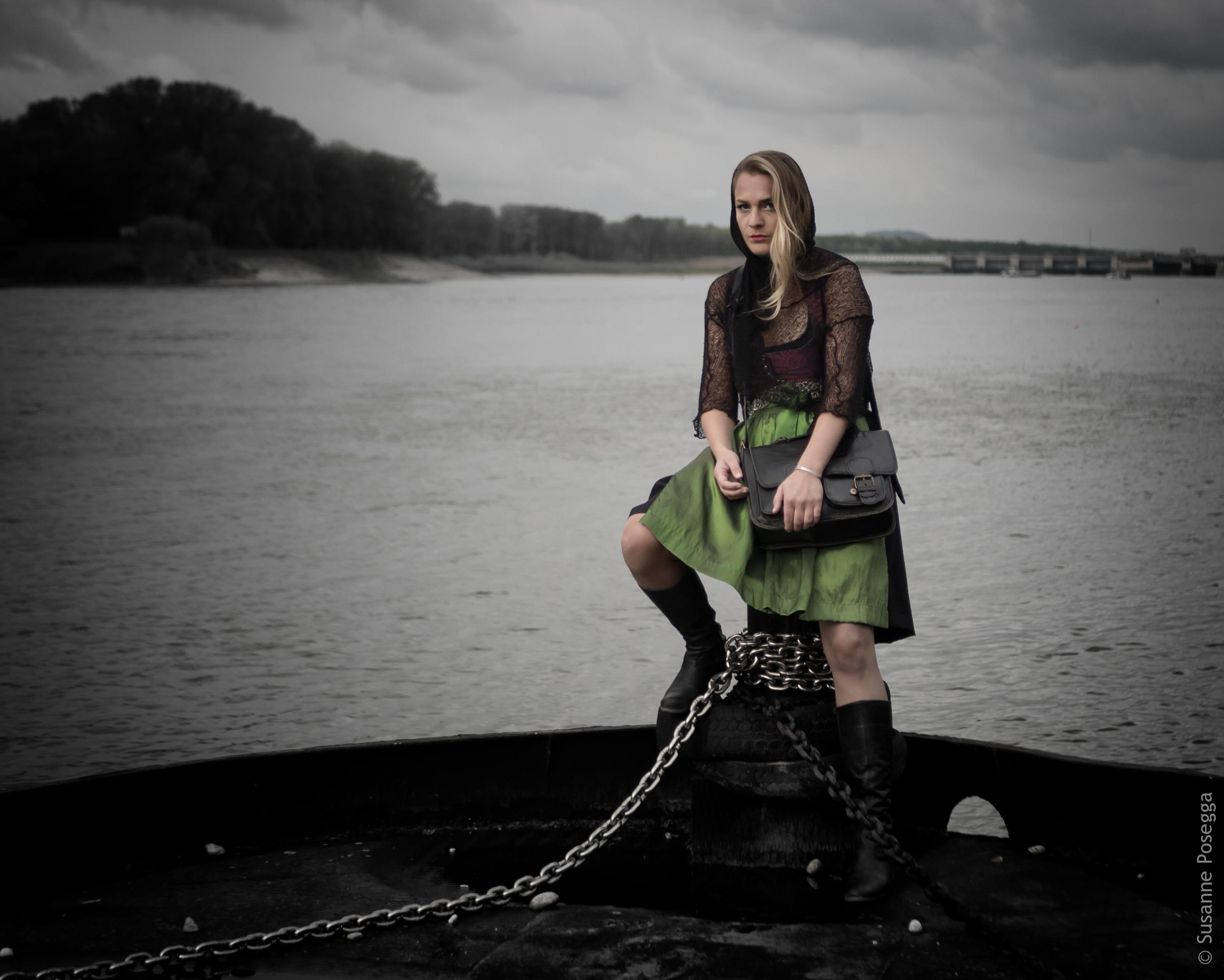 Model in Dirndl auf einem Schiff am Wasser. Düstere Stimmung im Hintergrund